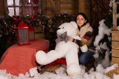 Muñeca grande del oso blanco del abarcamiento de la mujer joven Imagen de archivo