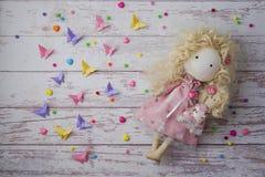 Muñeca hecha a mano de la tela cerca de las gotas coloridas, mariposas de papel imagenes de archivo