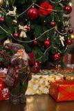 Muñeca linda de Santa Claus con una ruborización en las mejillas que sostienen un regalo Fotos de archivo