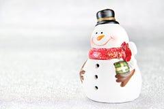 Muñeca linda del muñeco de nieve en el fondo de plata del papel del brillo Foto de archivo