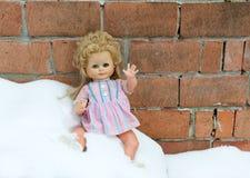 Muñeca perdida que miente en nieve fría fotos de archivo