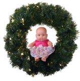 Muñeca que se sienta en la guirnalda de la Navidad Fotos de archivo
