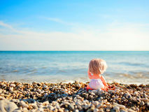 Muñeca que se sienta en la playa y que señala al mar Foto de archivo