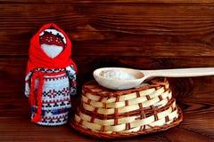 Muñeca rusa popular, una cuchara del arroz, una cesta, una tradición Viejo fondo de madera marrón Imagen de archivo