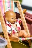 Muñeca vieja del verano en un pequeño deckchair en la calle justa fotos de archivo libres de regalías
