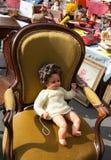Muñeca vieja en butaca de la felpa en el mercado de pulgas Imagen de archivo