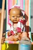 Muñeca vieja hermosa del verano en el pequeño deckchair para la nostalgia de la niñez imágenes de archivo libres de regalías