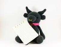 Muñeca y cuaderno del búfalo negro en el fondo blanco aislado Imagenes de archivo