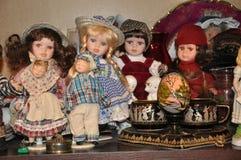 Muñecas de la porcelana en la compañía de amigos fotografía de archivo