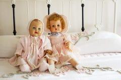 Muñecas de la vendimia en la colcha de Chanille en cama del hierro Foto de archivo