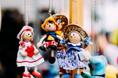 Muñecas de madera vestidas en diversos equipos muñecas de madera hechas a mano que cuelgan como exhibición Muñecas decorativas Fotos de archivo libres de regalías