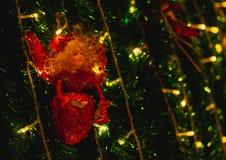 Muñecas en el árbol de navidad en día de la Navidad en la noche foto de archivo