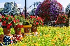 Muñecas en el césped delante de un macizo de flores Foto de archivo libre de regalías