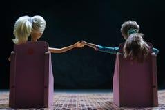 muñecas que se sientan en la parte posterior tomada de la mano imágenes de archivo libres de regalías