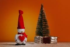 Muñeco de nieve, árbol de navidad y regalos sobre piso nevoso y fondo anaranjado Todavía de la Navidad vida Foto de archivo libre de regalías