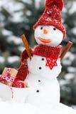Muñeco de nieve adornado con los regalos para la Navidad o la tarjeta del día de San Valentín en fondo del árbol conífero Imagenes de archivo
