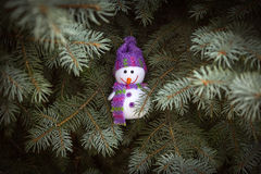 Muñeco de nieve alegre con una bufanda que oculta cerca de un árbol de navidad Foto de archivo libre de regalías