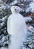 Muñeco de nieve alto con el sombrero delante de árboles nevados en la noche Fotografía de archivo
