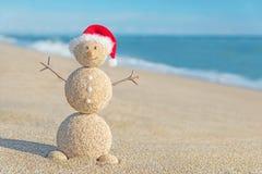 Muñeco de nieve arenoso sonriente en el sombrero de santa Concepto del día de fiesta por Años Nuevos Imagen de archivo libre de regalías
