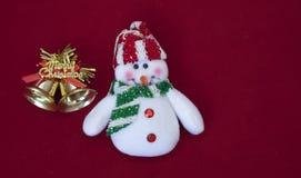 Muñeco de nieve blanco con las campanas de la Navidad del oro en fondo rojo Imagen de archivo