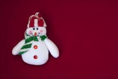 Muñeco de nieve blanco en un fondo rojo fotos de archivo libres de regalías