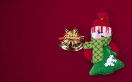 Muñeco de nieve blanco y verde con las campanas de la Navidad del oro en fondo rojo fotos de archivo libres de regalías