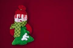 Muñeco de nieve blanco y verde en un fondo rojo imagen de archivo libre de regalías