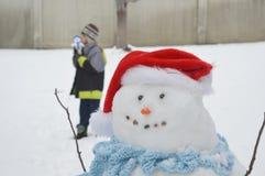 Muñeco de nieve con el niño en patio Fotos de archivo