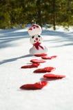 Muñeco de nieve con el sendero del corazón Foto de archivo