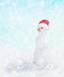 Muñeco de nieve con el sombrero de Papá Noel en caída de la nieve del invierno, Imagenes de archivo