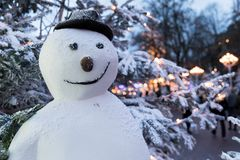 Muñeco de nieve con el sombrero delante de árboles nevados en la noche Imagen de archivo