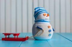 Muñeco de nieve con el trineo - decoración del tiempo de Navidad y Fotografía de archivo