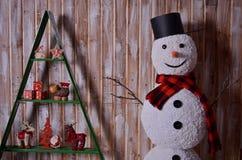 Muñeco de nieve con la bufanda y los juguetes rojos Foto de archivo libre de regalías