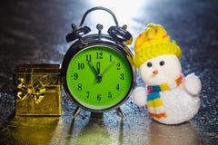 Muñeco de nieve con la caja de regalo y el despertador retro Imagenes de archivo
