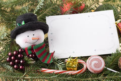 Muñeco de nieve con la tarjeta de Navidad en blanco Imagen de archivo