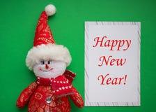 Muñeco de nieve con la tarjeta de Navidad en fondo verde Copie el espacio Decoraciones de la Navidad imagenes de archivo