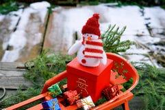 Muñeco de nieve con los regalos en un trineo Fotografía de archivo