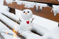 Muñeco de nieve con un corazón rojo en un banco nevoso Fotos de archivo