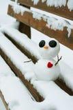 Muñeco de nieve con un corazón rojo en un banco nevoso Foto de archivo
