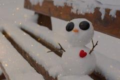 Muñeco de nieve con un corazón rojo en un banco nevoso Imagenes de archivo