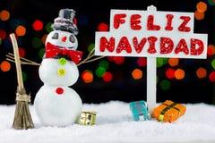 Muñeco de nieve con un poste indicador de la Feliz Navidad escrito en español Imagen de archivo