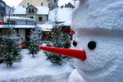 Muñeco de nieve con una nariz roja en la ciudad en la Navidad y el Año Nuevo Imagen de archivo libre de regalías