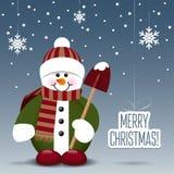 Muñeco de nieve con una pala en fondo nevoso Foto de archivo libre de regalías