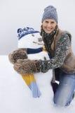 Muñeco de nieve de abarcamiento feliz de la mujer joven Imágenes de archivo libres de regalías