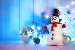 Muñeco de nieve de la Navidad con las bolas y guirnalda en el tablero de madera Fotos de archivo