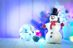 Muñeco de nieve de la Navidad con las bolas y guirnalda en el tablero de madera Fotografía de archivo libre de regalías