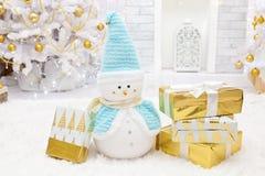 Muñeco de nieve de la Navidad con los regalos en el cuarto Foto de archivo