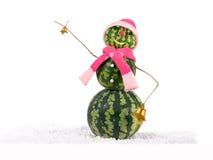 Muñeco de nieve de la Navidad de la sandía con dos campanas de oro en sombrero y bufanda rosados en la nieve Concepto del día de  Fotos de archivo libres de regalías