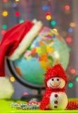 Muñeco de nieve de la Navidad en el fondo del globo en un casquillo de Santa Claus Imagen de archivo