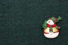 Muñeco de nieve de la Navidad en fondo verde de la tela Imagenes de archivo